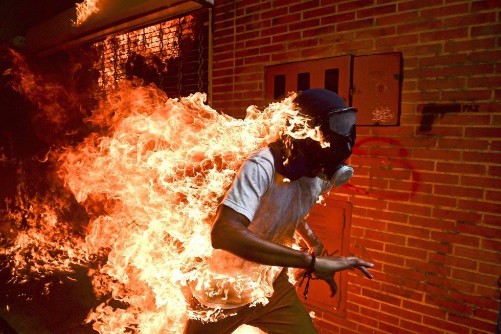 Um manifestante em chamas durante confrontos com policiais durante um protesto contra o presidente venezuelano Nicolás Maduro, em Caracas (Venezuela), no dia 3 de maio de 2017. Foto indicada nas categorias 'Foto do Ano' e 'Temas da atualidade', feita pelo fotógrafo Romaldo Schemidt, da agência France Presse (AFP).