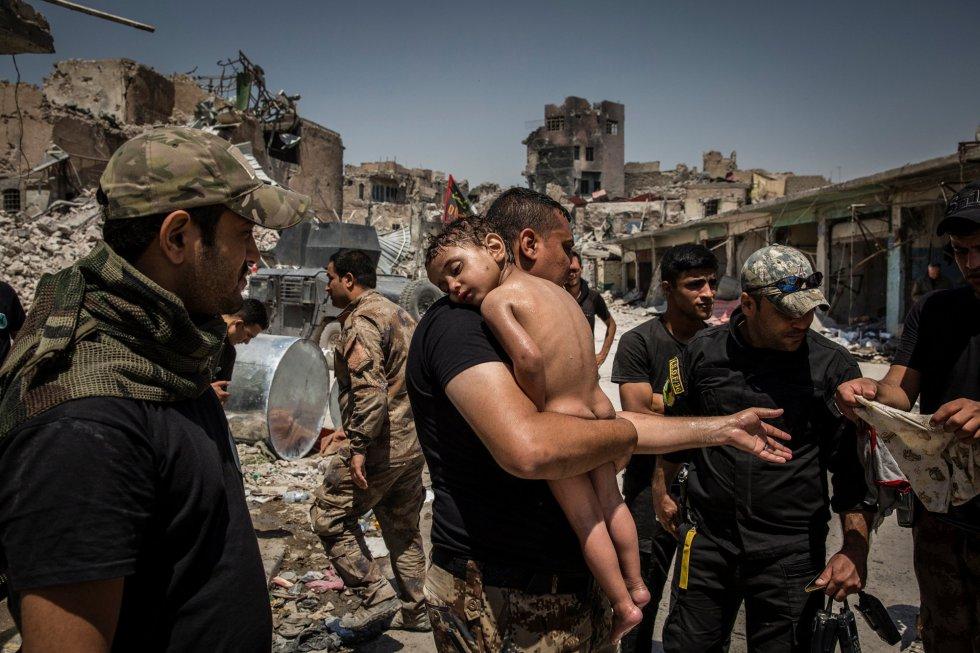 Criança de colo é evacuada da última área controlada pelo Estado islâmico na Cidade Velha de Mosul por um homem suspeito de ser militante, atendido por soldados das Forças Especiais do Iraque, em 12 de julho de 2017. Foto indicada na categoria 'Foto do Ano', feita pelo fotógrafo Ivor Prickett.