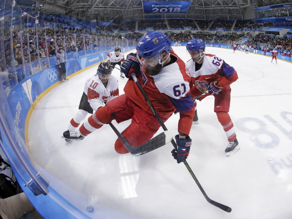 Adam Polasek (en primer término), de la República Checa, pelea por la pastilla con el suizo Andres Ambuhl, durante la ronda preliminar de hockey hielo, el 18 de febrero.