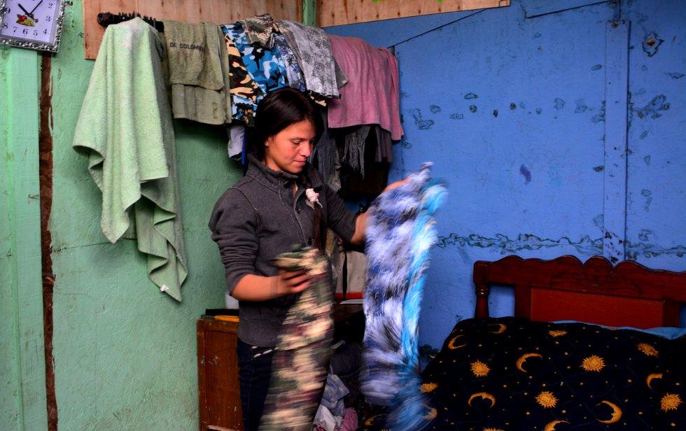 Jessica hizo crecer su negocio con un microcrédito. Otro más tarde le permitió diversificar para participar en el negocio de confección de ropa de su suegra. En su dormitorio, muestra algunas de las prendas que hacen. rn