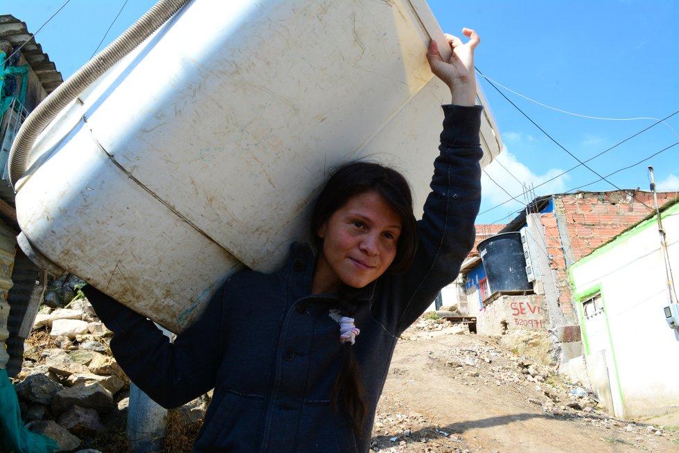 Jessica carga una lavadora para llevarla a casa de un vecino. Su espalda se resintió de este trabajo, así que ya no las alquila por horas, sino por días, lo que le ahorra viajes.rn
