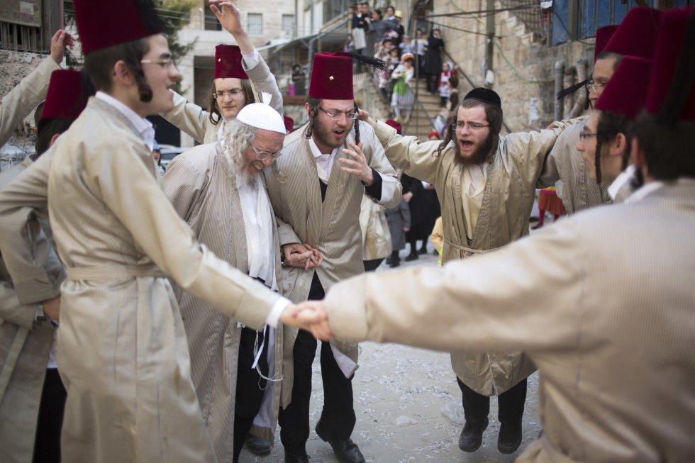 """Durante la jornada es común el consumo en grandes cantidades de alcohol, y es que la tradición establece que se beba """"hasta que no se distinga al bendito Mordejai (el héroe judío de la leyenda), del maldito Hamán"""". En la imagen, un grupo de judíos urltraortodoxos celebran la festividad de Purim, en el barrio Mea Shearim de Jerusalén, el 2 de marzo."""
