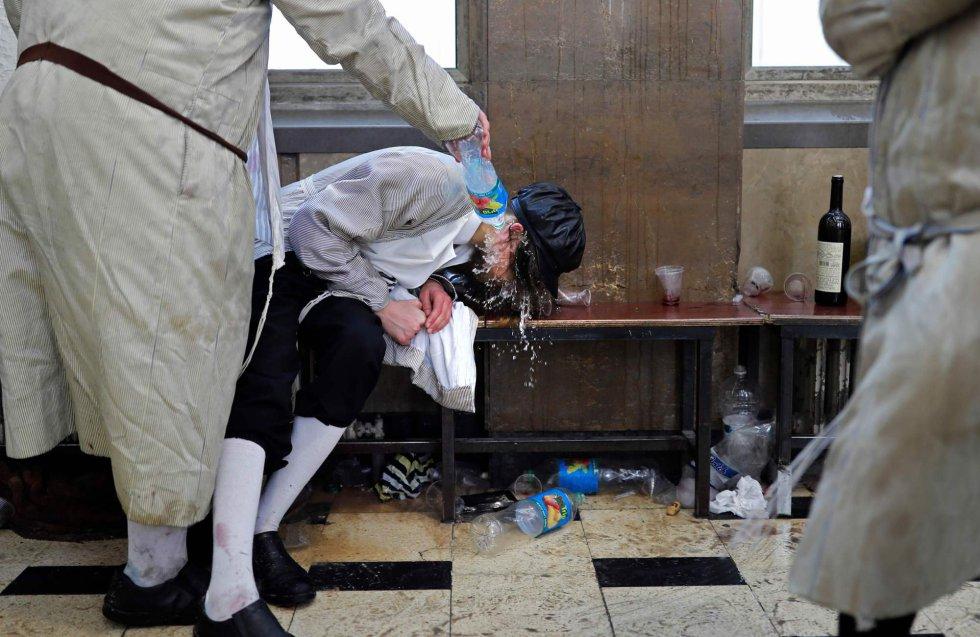 Según los preceptos religiosos, antes del inicio de Purim se celebra el ayuno de Esther, que se extiende el miércoles hasta la caída del sol, periodo en el que los creyentes acuden a las sinagogas para hacer lecturas bíblicas y oraciones festivas. En la imagen, un hombre judío ultraortodoxo arroja agua sobre un compañero borracho en el barrio ultraortodoxo de Jerusalén, Mea Sharim, el 2 de marzo.