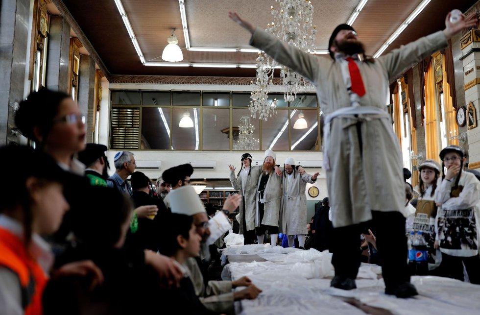En Jerusalén, la festividad se celebra un día más tarde que en el resto de ciudades, ya que la tradición establece que se tiene que conmemorar con una jornada de posterioridad en las urbes amuralladas. En la imagen, hombres judíos bailan en una escuela religiosa en el barrio ultraortodoxo de Jerusalén, Mea Sharim, el 2 de marzo.