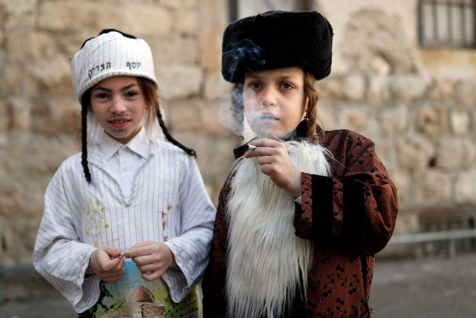 Ester, una mujer judía que en aquel momento era la reina de Persia, ayudó a evitar el genocidio sobre su pueblo después de que el visir convenciese al emperador persa de exterminar todos los judíos, dice la leyenda. En la imagen, dos niños disfrazados fuman un cigarrillo en el barrio ultraortodoxo Mea Sharim de Jerusalén, el 2 de marzo.