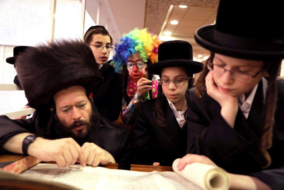 """Según los preceptos religiosos, antes del inicio de Purim, que simboliza la victoria del pueblo judío sobre """"la tiranía antisemita"""", se celebra el ayuno de Esther, periodo en el que los creyentes acuden a las sinagogas para hacer lecturas bíblicas y oraciones festivas. En la imagen, un niño disfrazado observa cómo judíos ultraortodoxos toman parte en la lectura del 'Libro de Esther', el 2 de marzo en Jerusalén."""