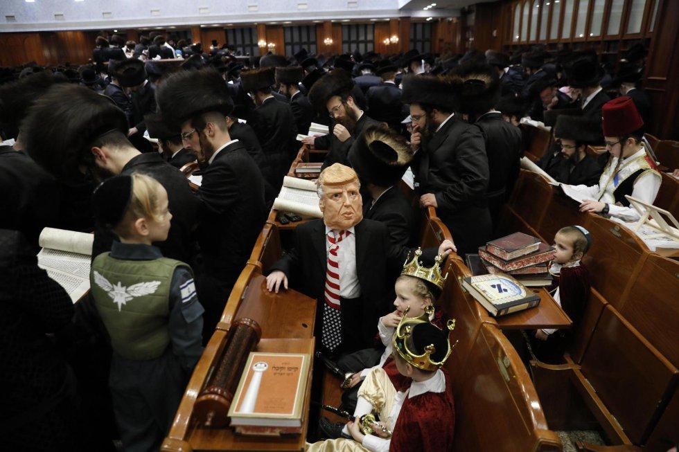 En este servicio religioso es costumbre que los fieles, sobre todo los niños, vayan a la sinagoga disfrazados. En la imagen, un niño judío ultraortodoxo disfrazado como el presidente de Estados Unidos, Donald Trump (centro), entre hombres que leen el 'Libro de Esthe'r, el 1 de marzo, en Jerusalén.