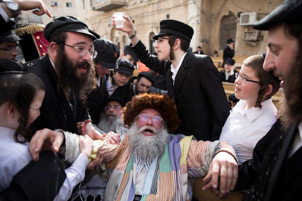Sin embargo, la reina consiguió interceder ante Asuero, el rey autorizó a los judíos que se defendieran y durante la jornada fijada para la ejecución, el día 13 del mes hebreo de Adar, la comunidad judía consiguió derrotar a sus enemigos. En la imagen, ultraortodoxos celebran la fiesta de Purim en una calle del barrio de Mea Shearim, en Jerusalén, el 2 de marzo.