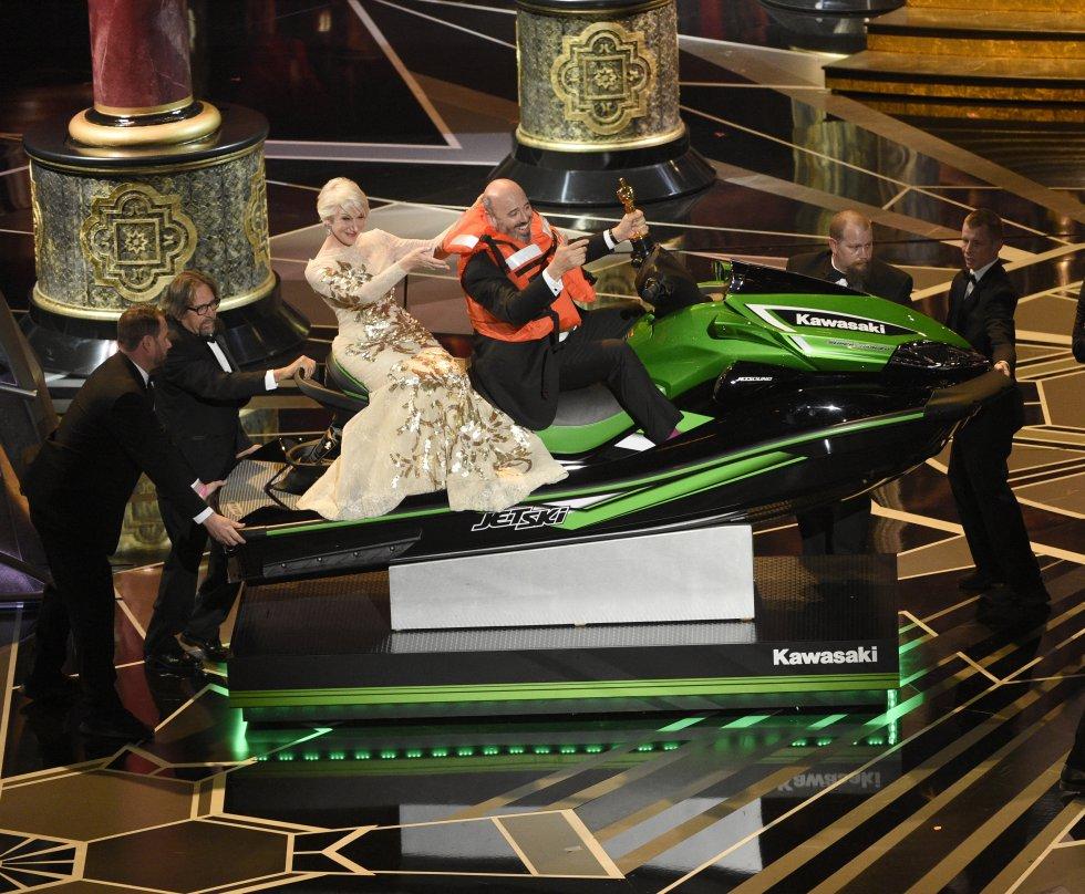 Helen Mirren acompañada de Mark Bridges, ganador del Oscar al mejor diseño de Vestuario, y ganador también de una moto acuática por pronunciar el discurso más corto.