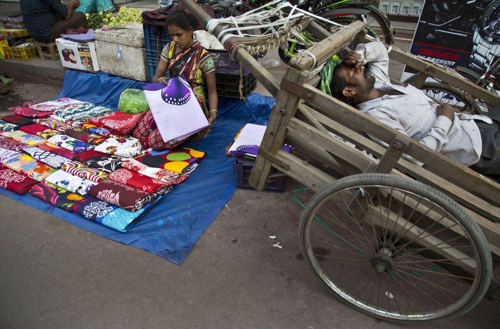Uma mulher indiana prepara a roupa que vai vender em seu posto de rua enquanto um homem dorme em uma carroça a seu lado em um mercado de Gauhati (Índia), no dia 7 de março.