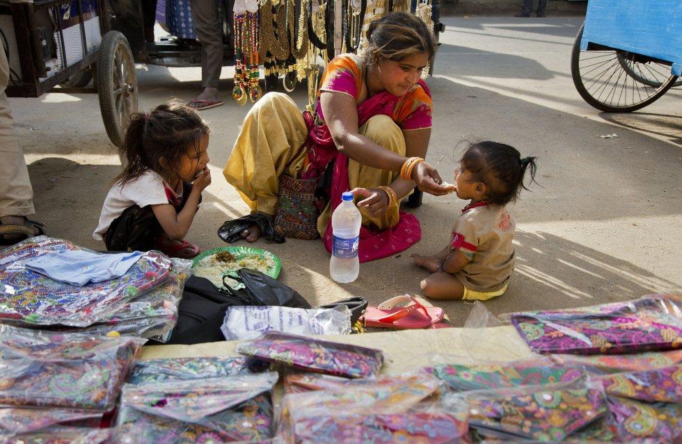 Uma vendedora ambulante alimenta seus filhos em Gauhati (Índia), em 7 de março.