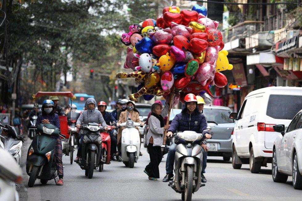 Una vendedora ambulante ofrece globos, en una calle de Hanói (Vietnam). Las flores y los globos son considerados los obsequios más populares que los hombres dan a las mujeres en el Día Internacional de la Mujer en Vietnam, que se conmemora anualmente el 8 de marzo.