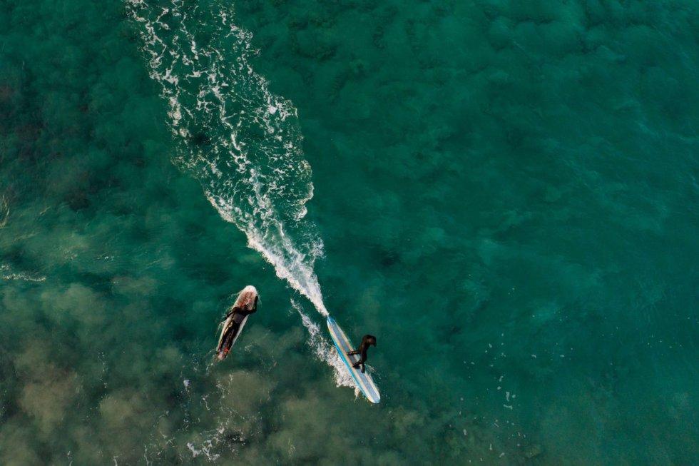 """Vista aérea de duas surfistas em Unstad, Ilhas Lofoten. """"Em 24 horas pode se viver todo tipo de experiências extraordinárias: fazer snowboard pela manhã, surfar pela tarde e admirar as auroras boreais à noite"""", explica Tommy Olsen, chefe do clube de surf de Unstad."""
