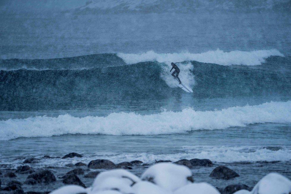Um surfista pega onda sob uma tempestade de neve em Unstad, Ilhas Lofoten.