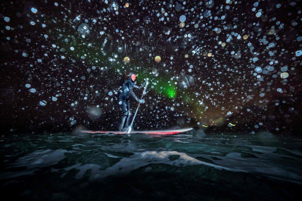 Myrtille Heissat faz padel surf sob uma aurora boreal em Unstad, nas Ilhas Lofoten.
