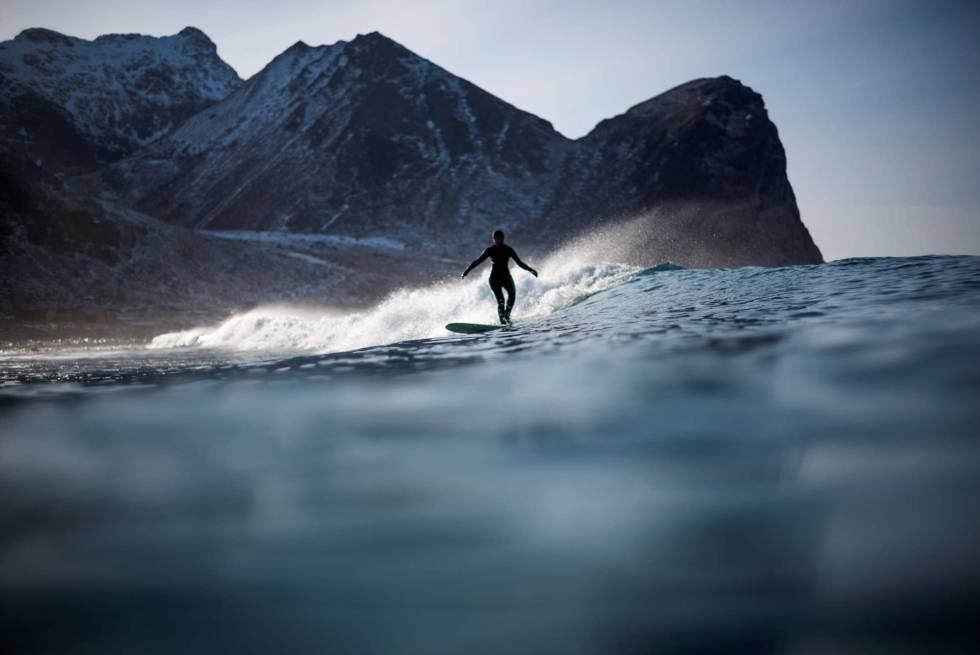 Nesta época do ano nas Ilhas Lofoten a água está a 4º e o ar a -15º. Na imagem, um surfista em Unstad, nas Ilhas Lofoten (Noruega).