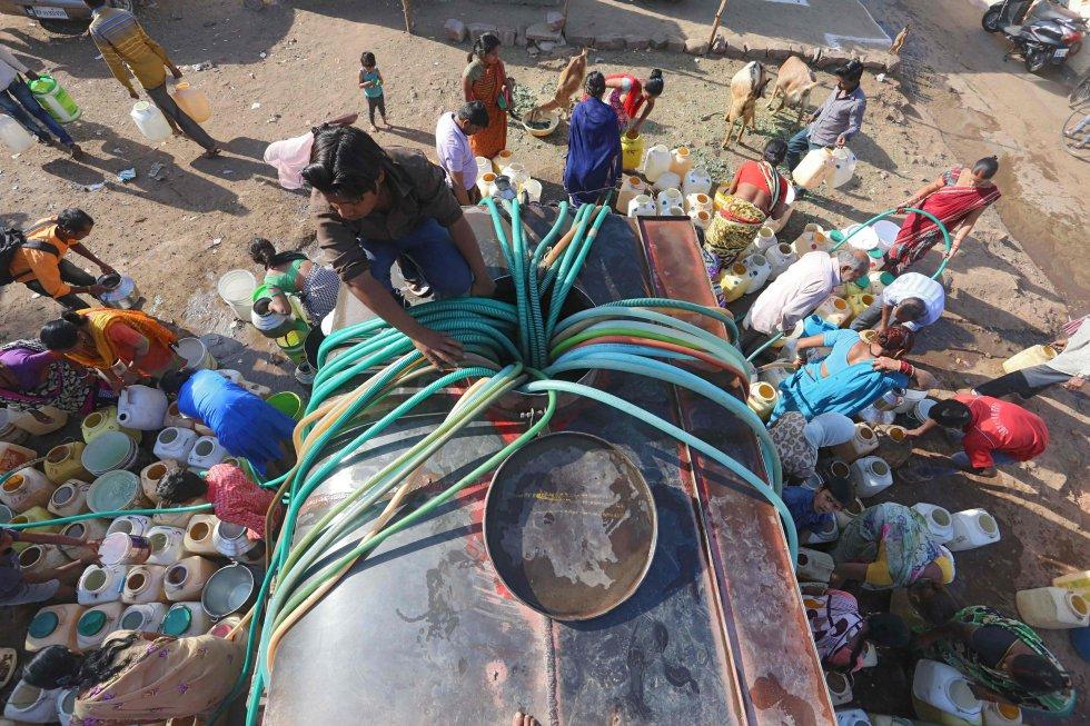 Habitantes de barrios marginados indios recogen agua potable de un buque cisterna municipal en la zona de Durga Nagar, en Bhopal, el 21 de marzo de 2018.