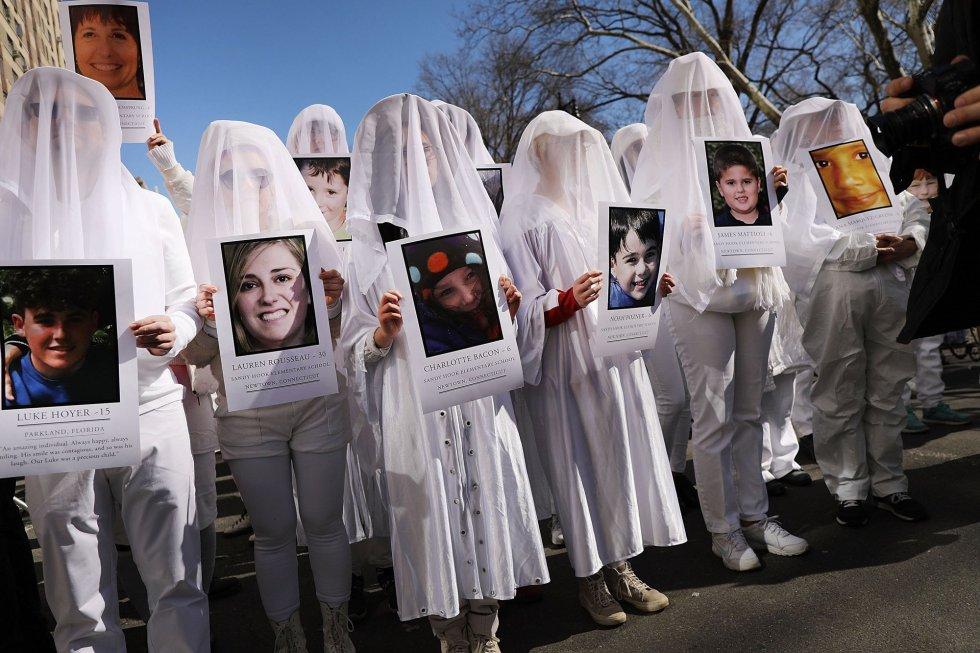 Niños sostienen fotos de personas asesinadas con armas de fuego duranta la protesta en Manhattan, Nueva York.