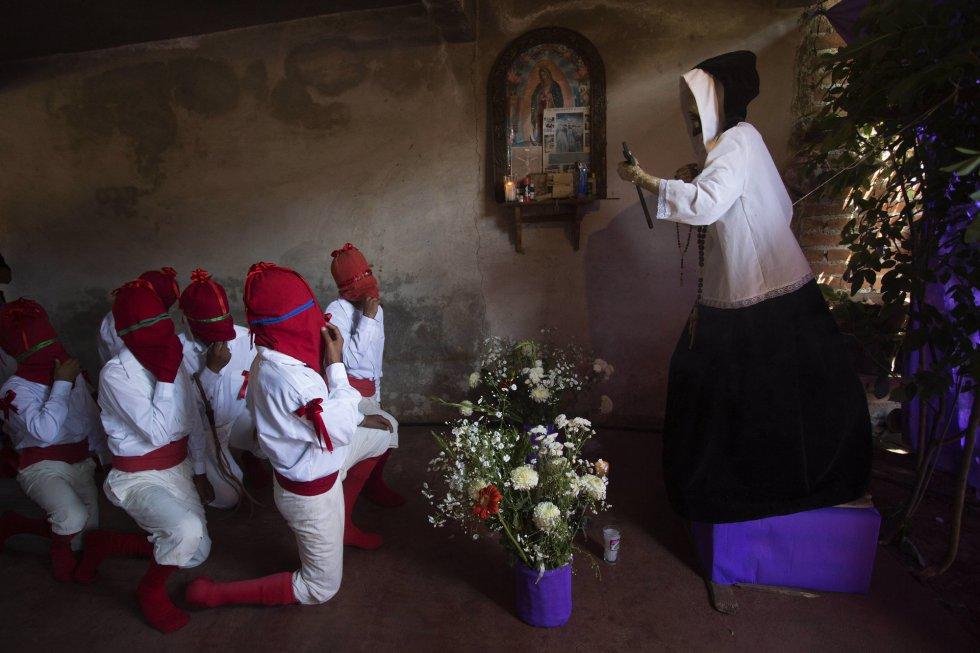 """Habitantes del poblado de Tzintzuntzan participan en un acto religioso, el 29 de marzo, en el marco de las celebraciones de Semana Santa en el estado de Michoacán (México). En el pasaje bíblico, el miércoles y jueves Santo Salen los """"espías"""" encapuchados en rojo y blanco, portando silbatos y buscando a Cristo para apresarlo."""