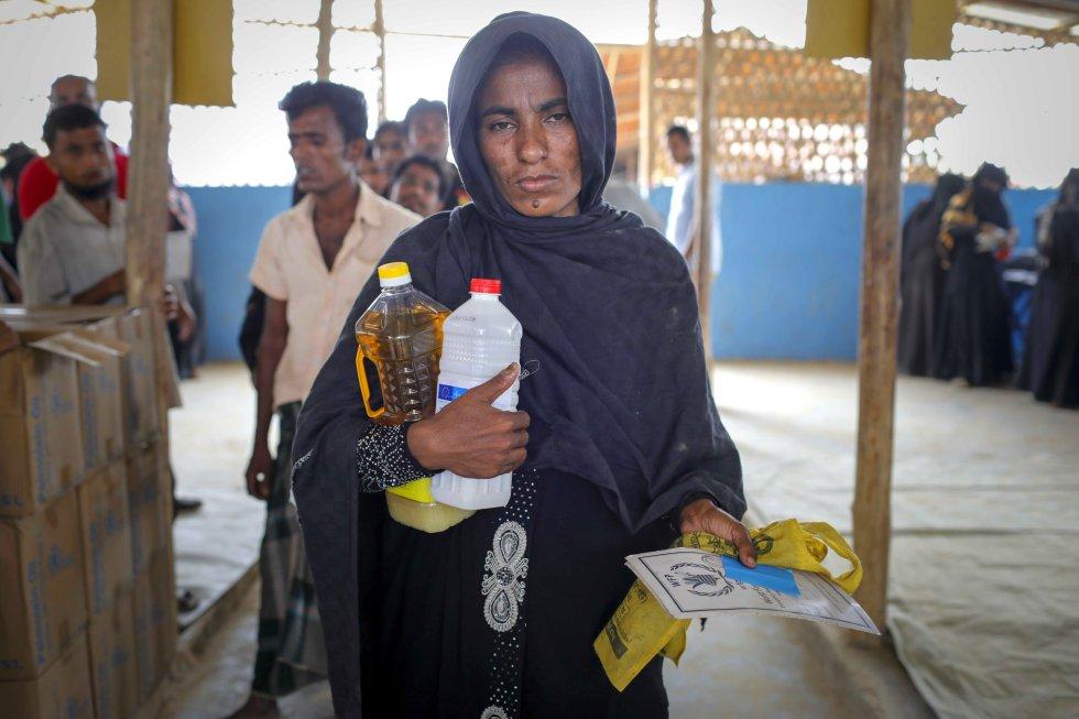 Una rohinyá recoge en un centro de distribución de comida del Programa Mundial de los Alimentos la ración mensual de su familia.