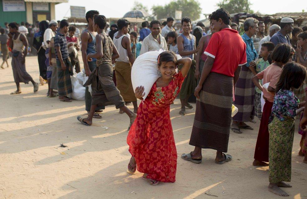 Una niña recoge el saco de arroz que corresponde cada mes a cada familia rohinyá en los campos de refugiados de Bangladés.