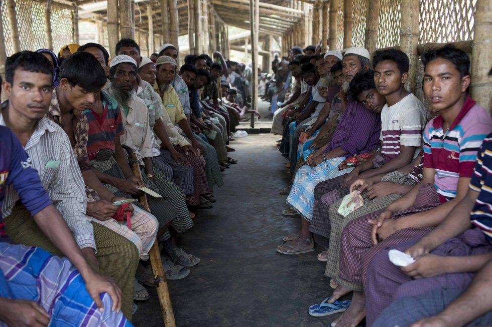 Un grupo de hombres rohinyás recién huidos a Bangladés desde Myanmar espera en el centro de tránsito de Acnur en el campo de Kutupalong.