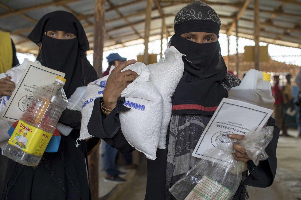 Dos refugiadas recogen las raciones mensuales de sus familias en uno de los centros de distribución del Programa Mundial de los Alimentos.