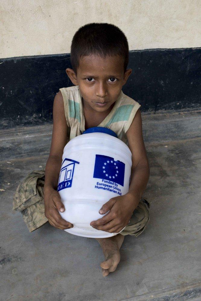 Un niño con un recipiente de ayuda donada por ECHO, la agencia humanitaria de la Unión Europea.
