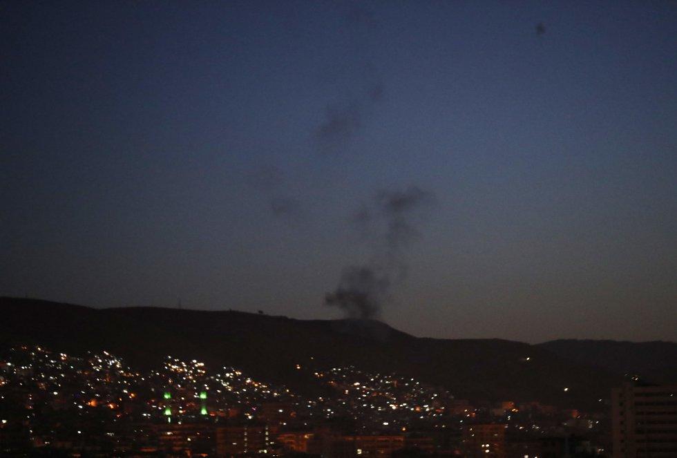 Una columna de humo sobre instalaciones militares del régimen sirio en Damasco.