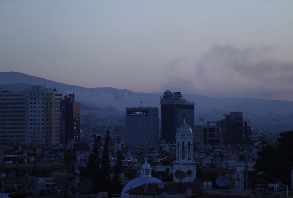 Columnas de humo salen de varios edificios de la capital de Siria tras los bombardeos.