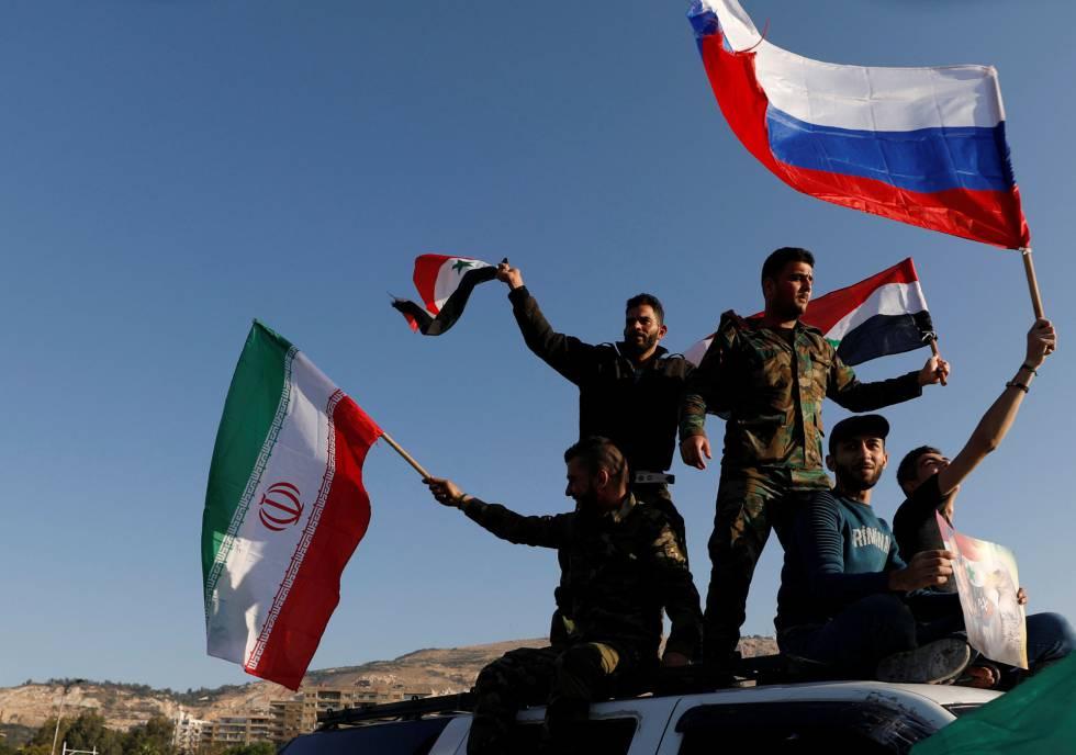 Ciudadanos sirios ondean banderas iraníes, rusas y sirias durante una protesta contra el ataque de EE UU.