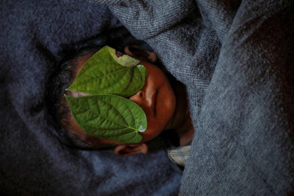 Rosto de um menino de 11 meses é coberto com folhas da pimenteira 'piper betle' depois de morrer lutando contra febre alta e tosse no campo de refugiados de Balukhali, perto do Cox's Bazar (Bangladesh), em 4 de dezembro de 2017.