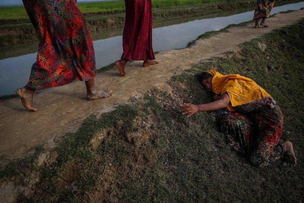 Um exausto refugiado que foge da violência em Mianmar pede ajuda àqueles que cruzam para Palang Khali, perto do Cox's Bazar (Bangladesh), em 2 de novembro de 2017.