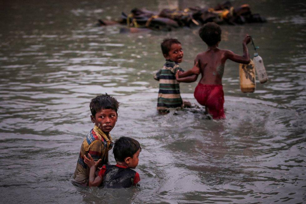 Os irmãos fogem da violência enquanto cruzam o rio Naf, ao longo da fronteira entre Bangladesh e Mianmar, em Palong Khali, perto do Cox's Bazar (Bangladesh), em 1º de novembro de 2017.