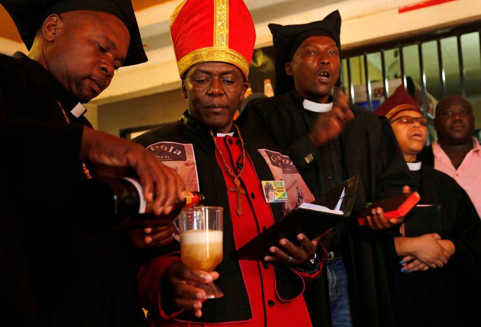 El líder de la Iglesia de Gabola, autoproclamado papa, Tsietsi Makiti (segundo a la izquierda), se prepara para bautizar a los recién llegados a esta comunidad durante un servicio en un bar en Orange Farm, al sur de Johannesburgo, el domingo 15 de abril de 2018. Esta nueva iglesia en Sudáfrica celebra el consumo de alcohol y ofrece servicios entusiastas y alimentados con alcohol en bares, para aquellos que han sido rechazados por otras parroquias porque beben.