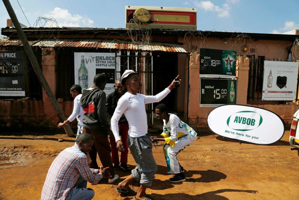 Los adoradores cantan y bailan himnos fuera del bar durante un servicio en Orange Farm, al sur de Johannesburgo, el domingo 15 de abril de 2018.