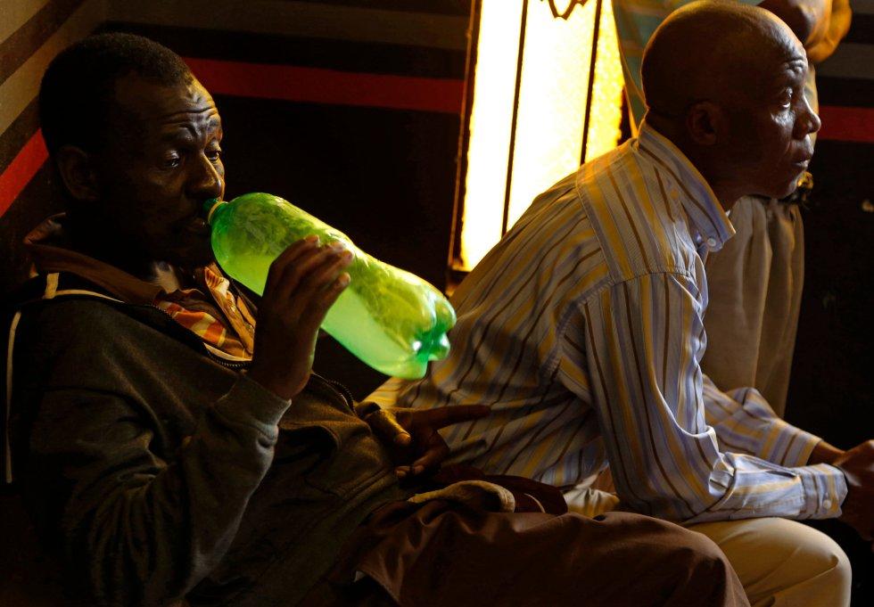 Un seguidor de la Iglesia de Gabola bebe una bebida casera de una botella de refresco durante un servicio en un bar en Orange Farm (Sudáfrica).