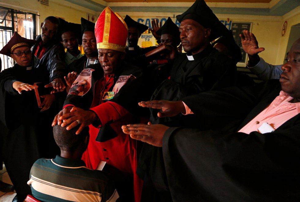 El líder de la Iglesia de Gabola, el autoproclamado papa Tsietsi Makiti, unge con cerveza a un recién llegado a la comunidad durante un servicio.