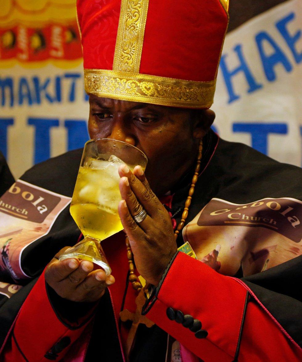 Makiti bebe de un cáliz durante la misa que está celebrando en un bar de Orange Farm.