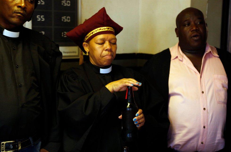 Una clériga de la Iglesia de Gabola bendice una botella de cerveza antes de ser consumida durante un servicio religioso en un bar en Orange Farm, al sur de Johannesburgo, el domingo 15 de abril de 2018.