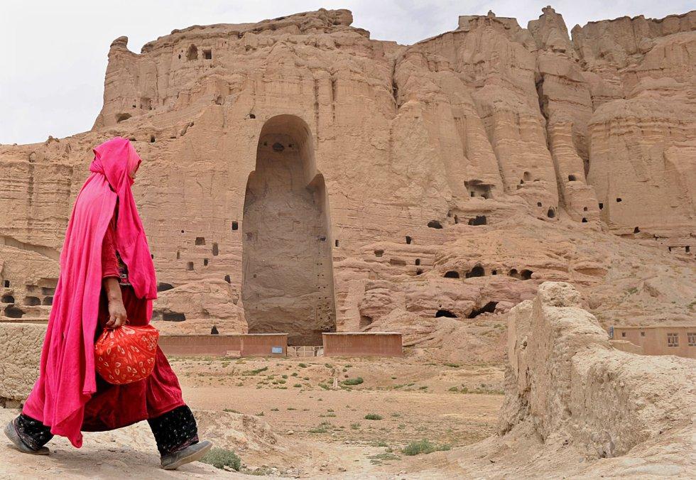 Una mujer afgana pasa frente a las ruinas de las antiguas estatuas de Buda en la ciudad de Bamiyán, el 1 de agosto de 2010.