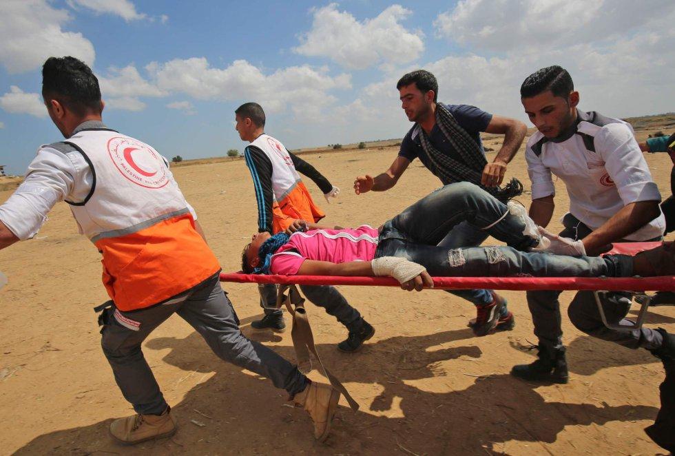 Desde que comenzó dicha marcha, el pasado 30 de marzo, las fuerzas israelíes han abatido al menos 45 palestinos, según fuentes sanitarias palestinas, mientras que del lado israelí no se han producido víctimas. En la imagen, varios palestinos llevan a un manifestante herido durante los enfrentamientos con las fuerzas israelíes, en frontera con la Franja de Gaza, el 14 de mayo de 2018.