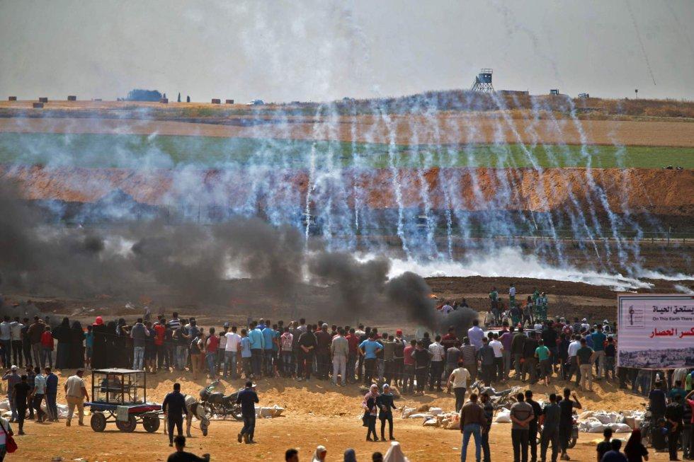Está previsto que las protestas culminen este martes, el día que los palestinos conocen como 'Nakba' (catástrofe) cuando, en 1948, comenzó el éxodo de cientos de miles de ellos de sus hogares por la creación del Estado de Israel. En la foto, los manifestantes palestinos observan el gas lacrimógeno y el humo de las llantas en llamas, al este de la ciudad de Gaza, el 14 de mayo de 2018.