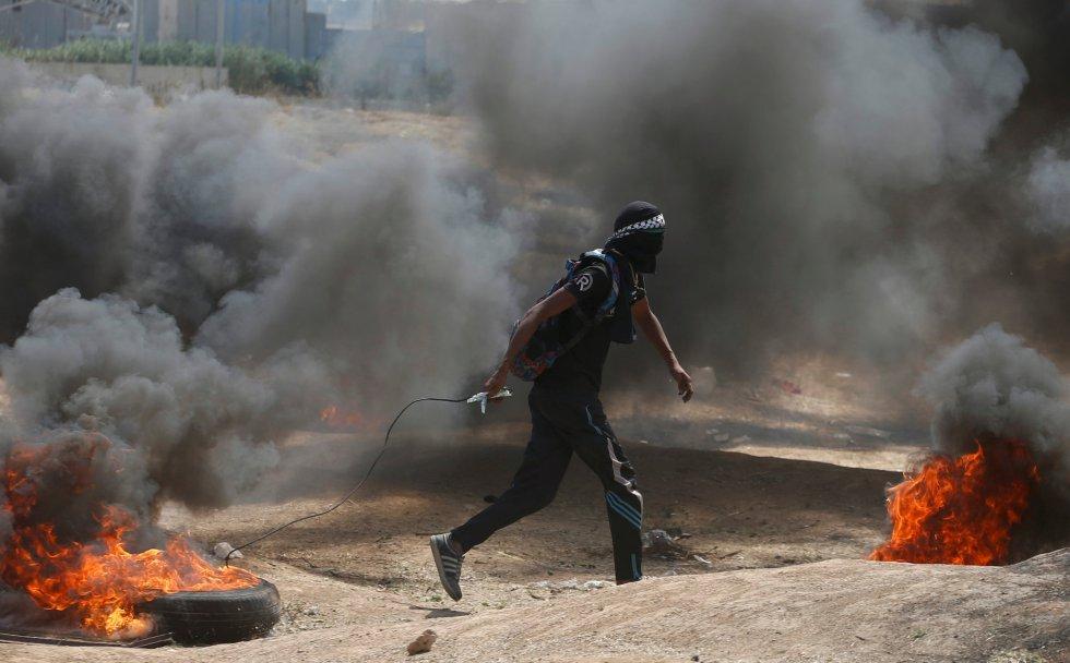 """Está previsto que las protestas vayan en aumento a lo largo del día, el 70 aniversario de la creación de Israel, mientras los altavoces de las mezquitas de Gaza llaman a los palestinos a sumarse a la llamada 'Gran marcha del retorno"""". En la fotografía, un manifestante palestino arrastra un neumático en llamas durante la protesta, en la frontera entre Gaza e Israel, el 14 de mayo de 2018."""