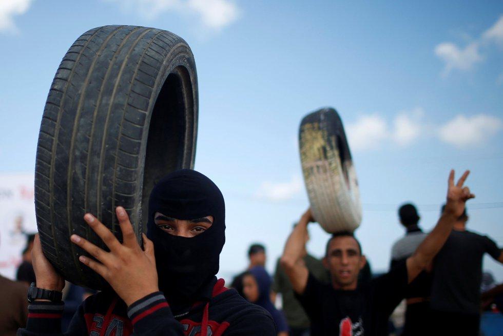 El Ejército israelí argumenta que sus tropas están defendiendo la frontera y disparando conforme con las normas de enfrentamiento. En la fotografía, manifestantes palestinos sujetan neumáticos, en la frontera entre Gaza e Israel, el 14 de mayo de 2018.