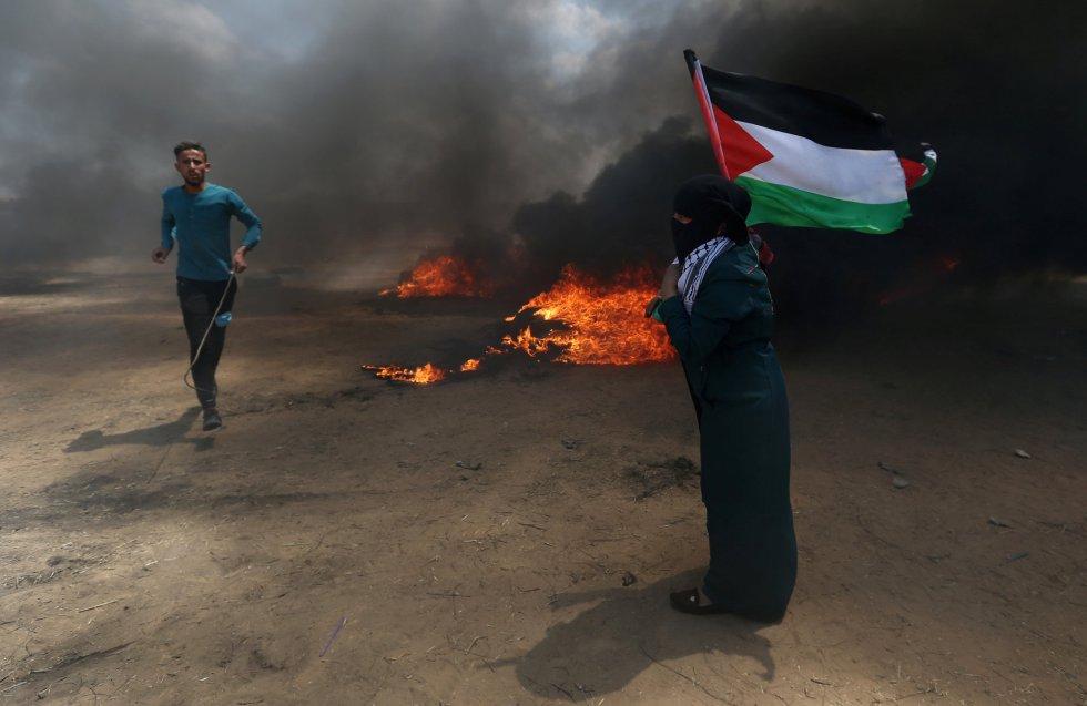"""El ministro de Educación israelí, Naftali Bennett, ha declarado que Israel tratará la valla fronteriza con Gaza como un """"muro de hierro"""" y que cualquiera que se acerque a ella será tratado como """"un terrorista"""". En la foto, una mujer sostiene una bandera de Palestina durante la protesta, el 14 de mayo de 2018."""