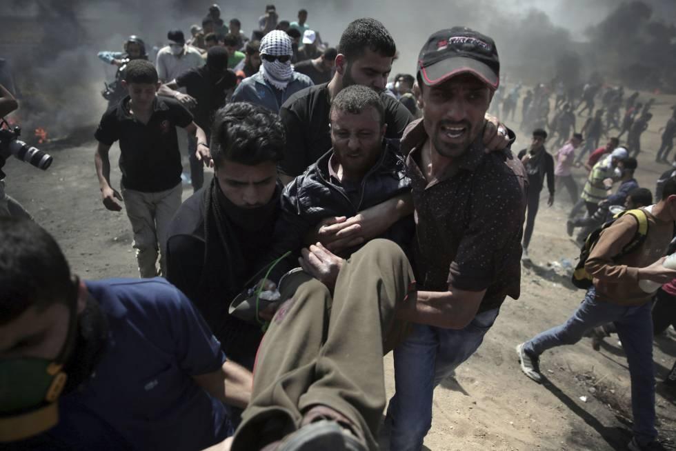 Un herido es trasladado por manifestantes durante la protesta entre la frontera de Gaza con Israel, el 14 de mayo de 2018.