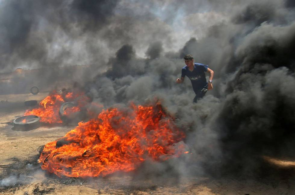 Un palestino camina entre el humo de unos neumáticos ardiendo durante la protesta en la frontera entre Gaza e Israel, el 14 de mayo de 2018.