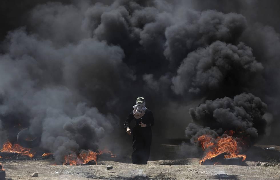 Una mujer camina entre el humo de unos neumáticos ardiendo durante la protesta en la frontera entre Gaza e Israel, el 14 de mayo de 2018.