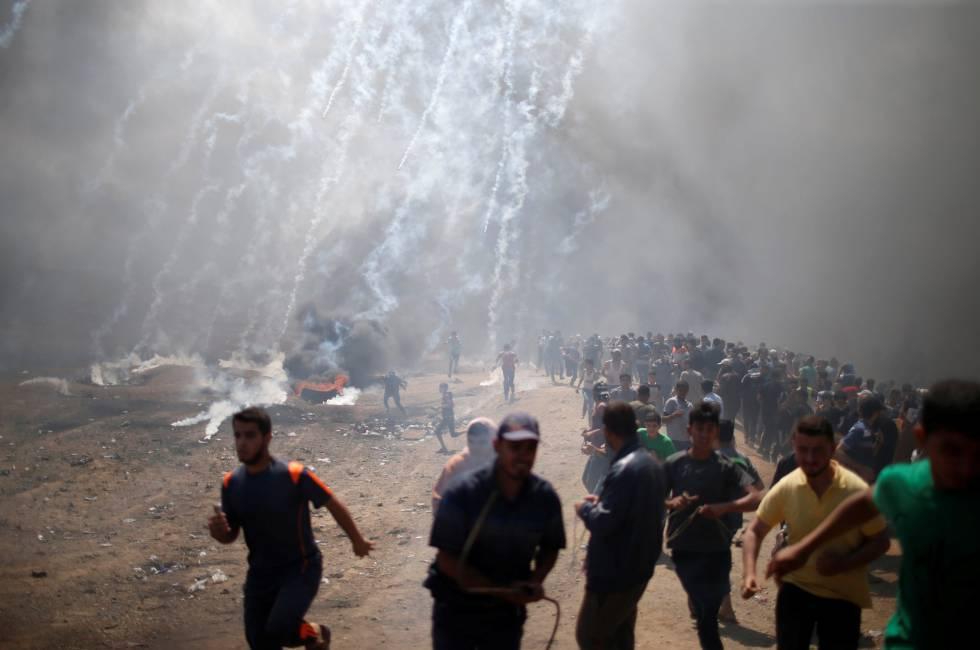 Un grupo de palestino corre durante el lanzamiento de botes de gas lacrimógeno por parte del Ejército de Israel en la frontera, el 14 de mayo de 2018.